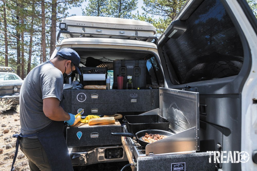 Man cooks using camp kitchen setup in back of vehicle.