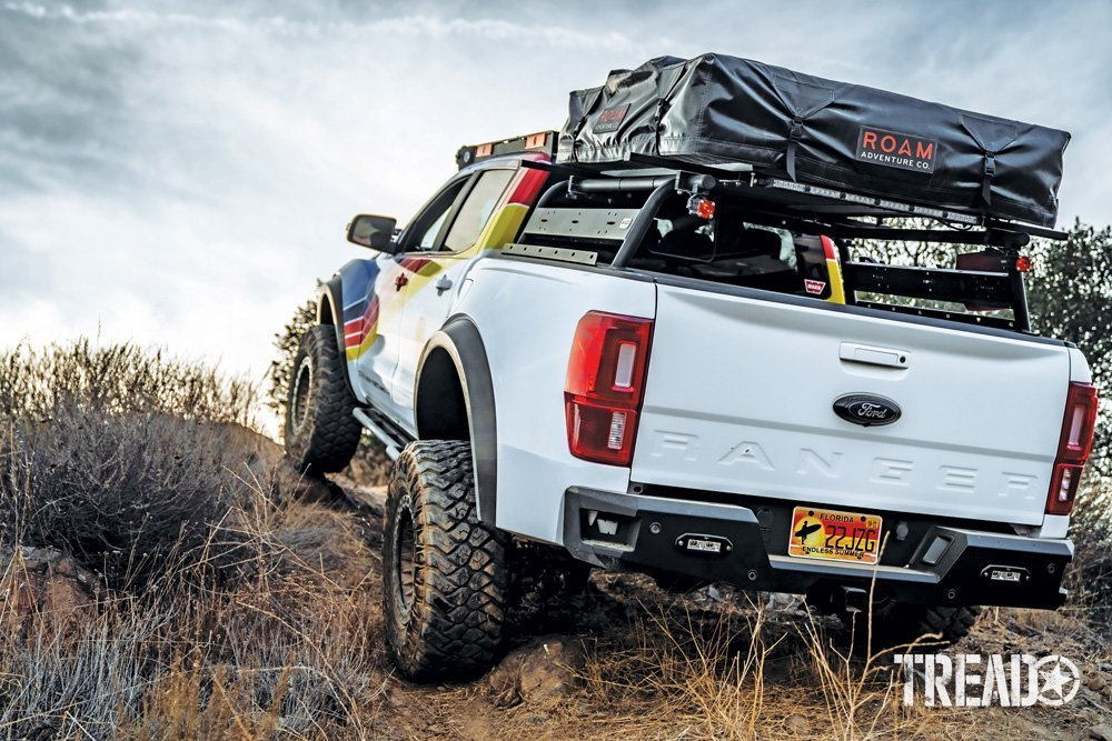 The multi-colored customized Ford Ranger showcases a truck bed rack, roof top tent, and is climbing a hill.