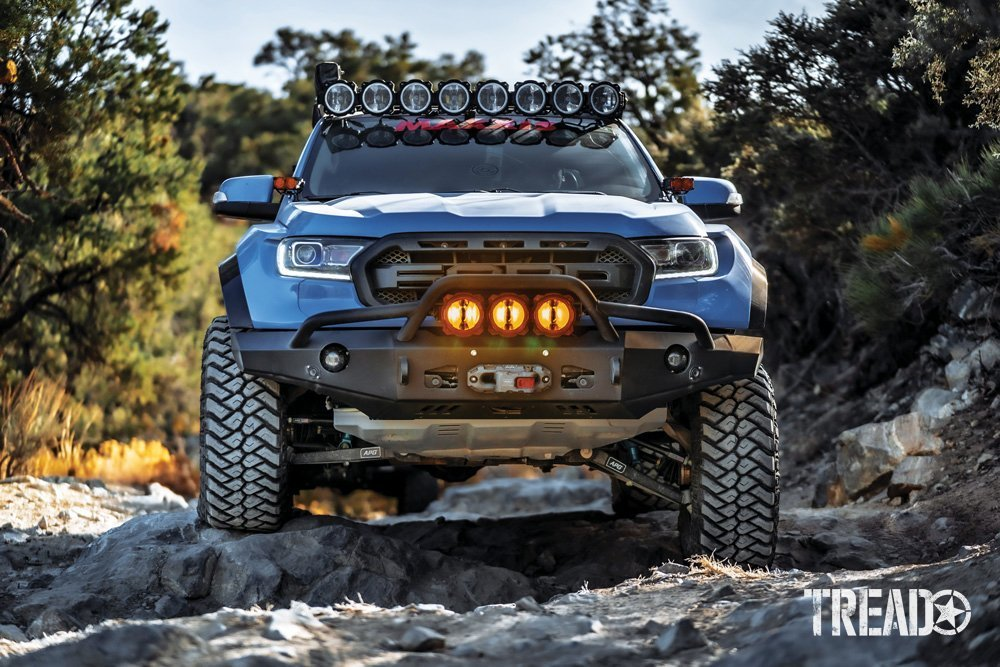 Head on shot of this customized 2019 Ford Ranger shows aftermarket bumper, lights, winch, and knobby tires