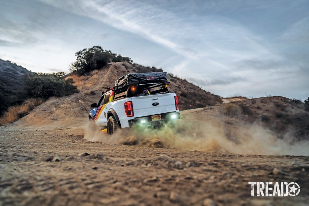 2019 Ford Ranger driving in dirt, its suspension compressed by taking a turn, dirt flying up in the air.