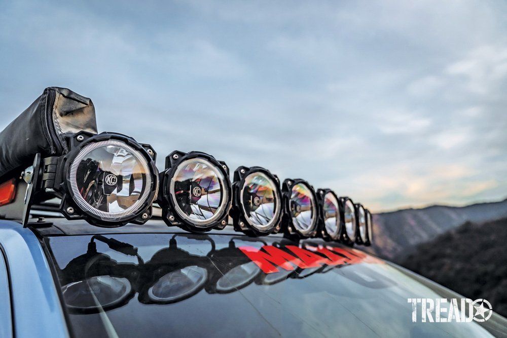 An array of KC HiLiTES aux driving lights are mounted on the 2019 Ford Ranger's roof rack, next to an awning.