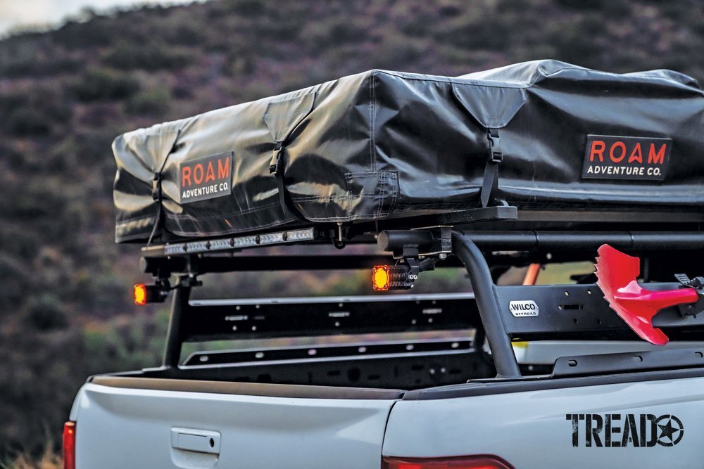 A ROAM rooftop tent in a black cover and black Wilco bed rack adorn the rear of a 2019 Ford Ranger.