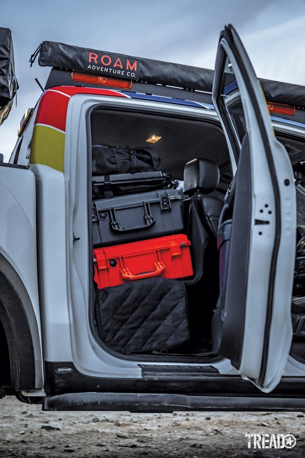 Gray and red Pelican cases in the 2019 Ford Ranger with the door opened.