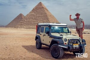 Dan Grec stands on his Jeep with pyramids in background.
