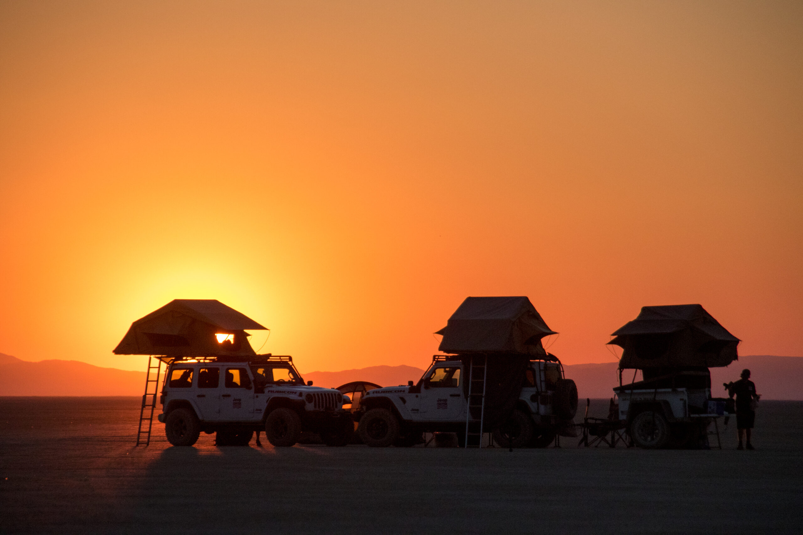 Two jeeps with rooftop tents camp on a dry lake bed at sunset.