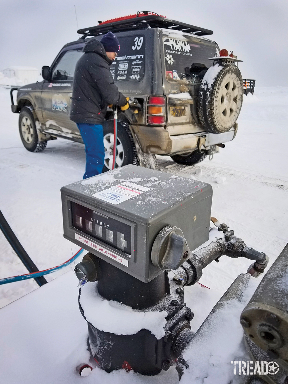 Andy Lilienthal, earing blue snow pants and black jacket fills up the dark gray Mitsubishi Pajero fuel tank and aux tank during the 2020 Alcan Rally.