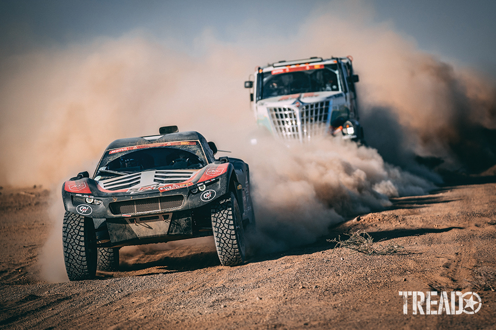 2021 Dakar Team #348 (Alexandre Leroy) drove in dusty dirt roads ahead of massive truck.