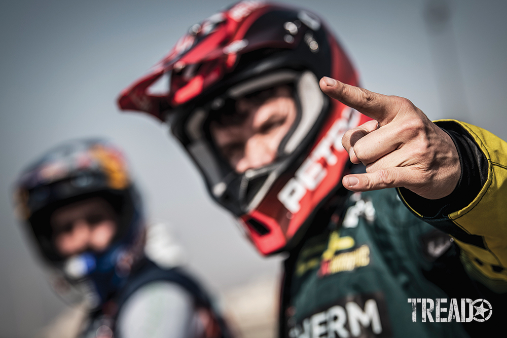 Outfitted with a helmet and black and yellow race suit, 2021 Dakar Simon Marcic of Team #46 in Jeddah motions with his hand.