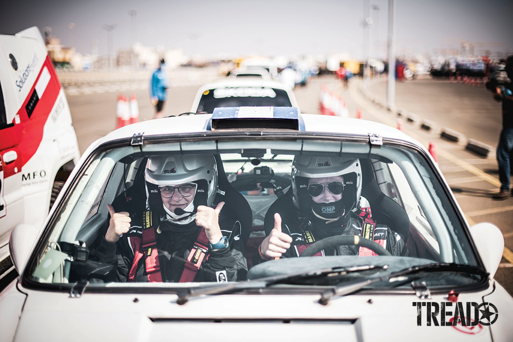 Amy Lerner (driver) and Sara Bossaert (co-driver) of Team #202 AL Rally give thumbs up while parked in Lerner's Porsche rally car.