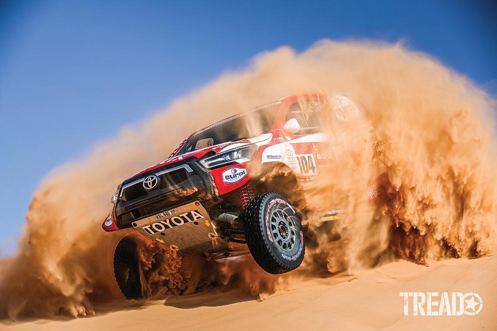 2021 Dakar ralliers in red and white Toyota, 304 De Villiers Giniel (zaf), Haro Bravo Alex (esp), crash through a huge sand dune in plume of dust.