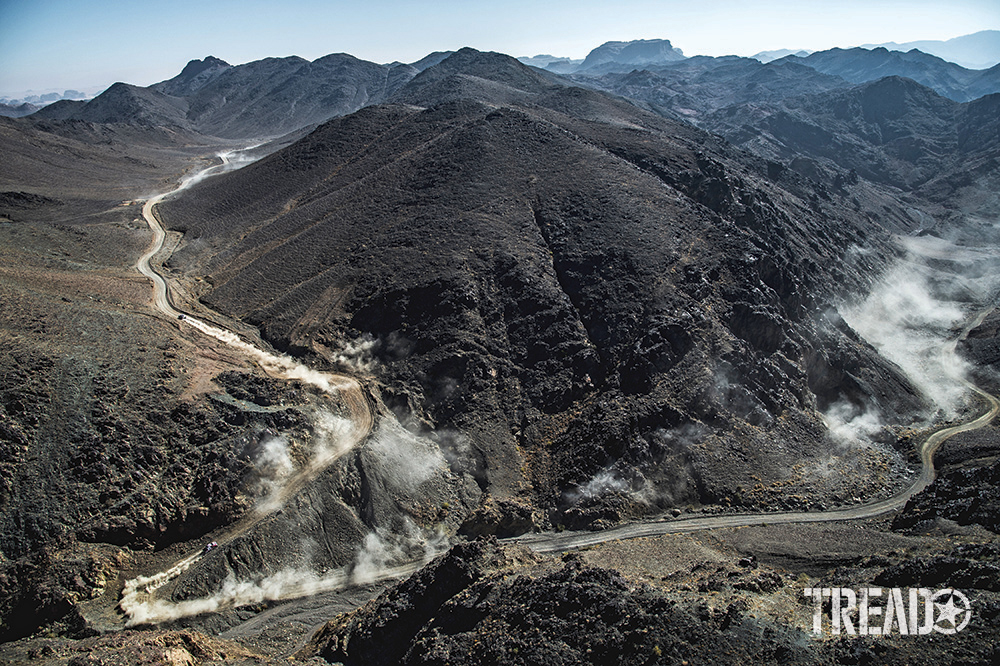 During the ninth stage of the Dakar 2021 between Neom and Neom, Saudi Arabia, teams raise dust as they curve around huge mountainsides.