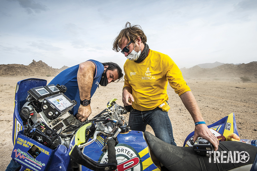 Dakar Rally Director David Castera works on a blue, black, and yellow motorbike during the 11th stage of the Dakar 2021.