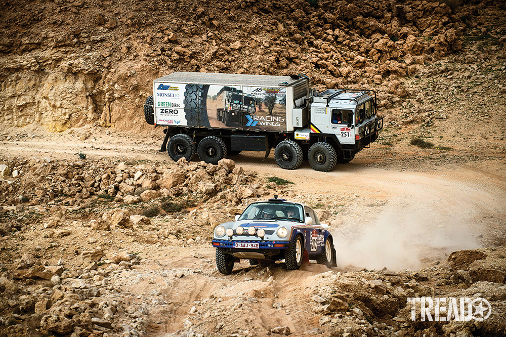 Team Lerner's blue and white #202 Porsche rallies ahead of a MAN truck competing as a Classic entry in the truck category.