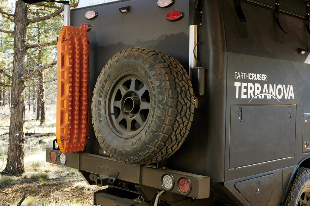 A full size spare tire and recovery boards mounted to the back of Terranova camper..