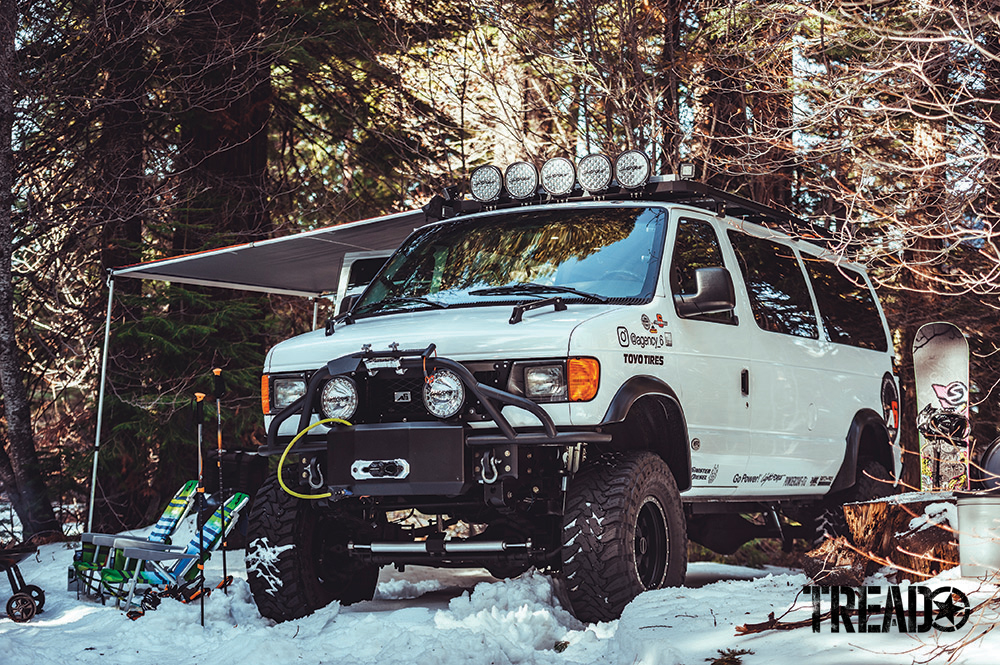 This Ford E350 Super Duty van is sitting in snow with awning set up.