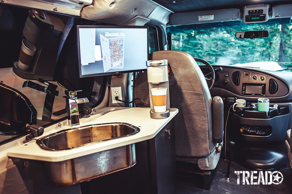 A Keurig coffee maker, as well as a sink and monitor on a white countertop, is anchored next to the van's window on the interior.