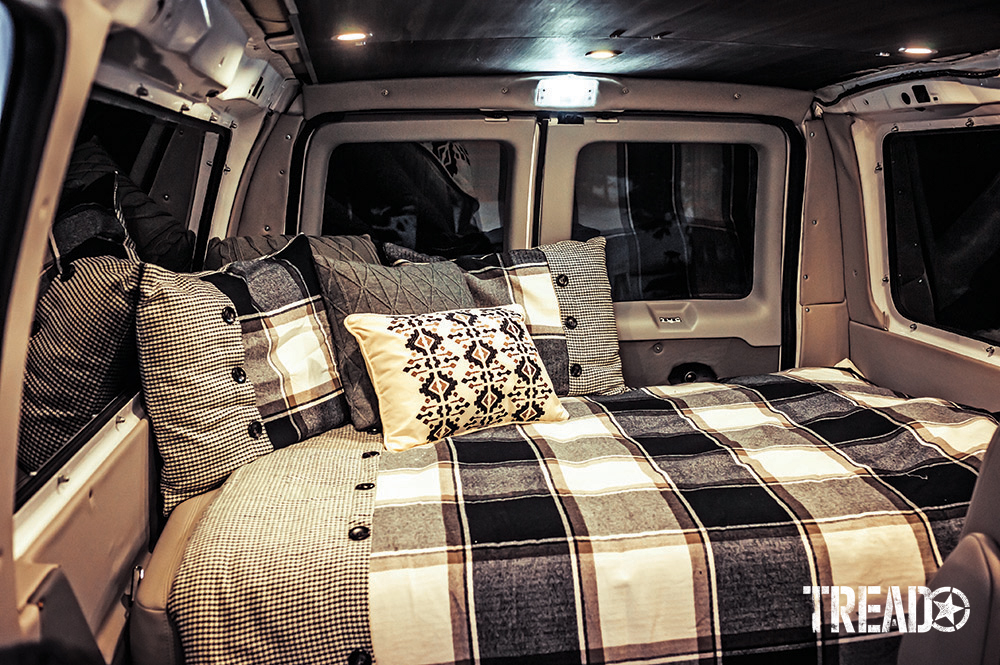2006 Ford E350 Super Duty 4x4 sleeping area includes several pillows and a black and white oversized checkerboard blanket with buttons.