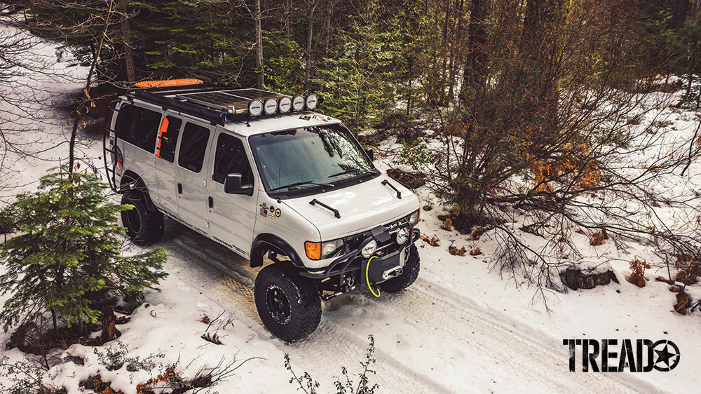 Two solar panels and orange recovery boards are mounted to a platform roof rack on a white 4x4 van.