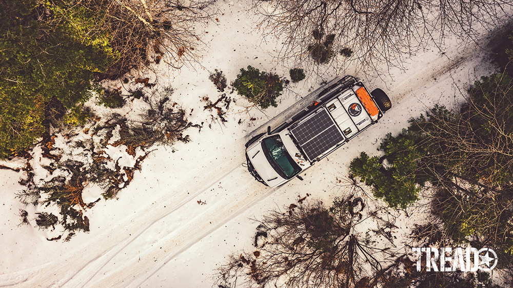 A bird's-eye view of white van driving on snowy trail.