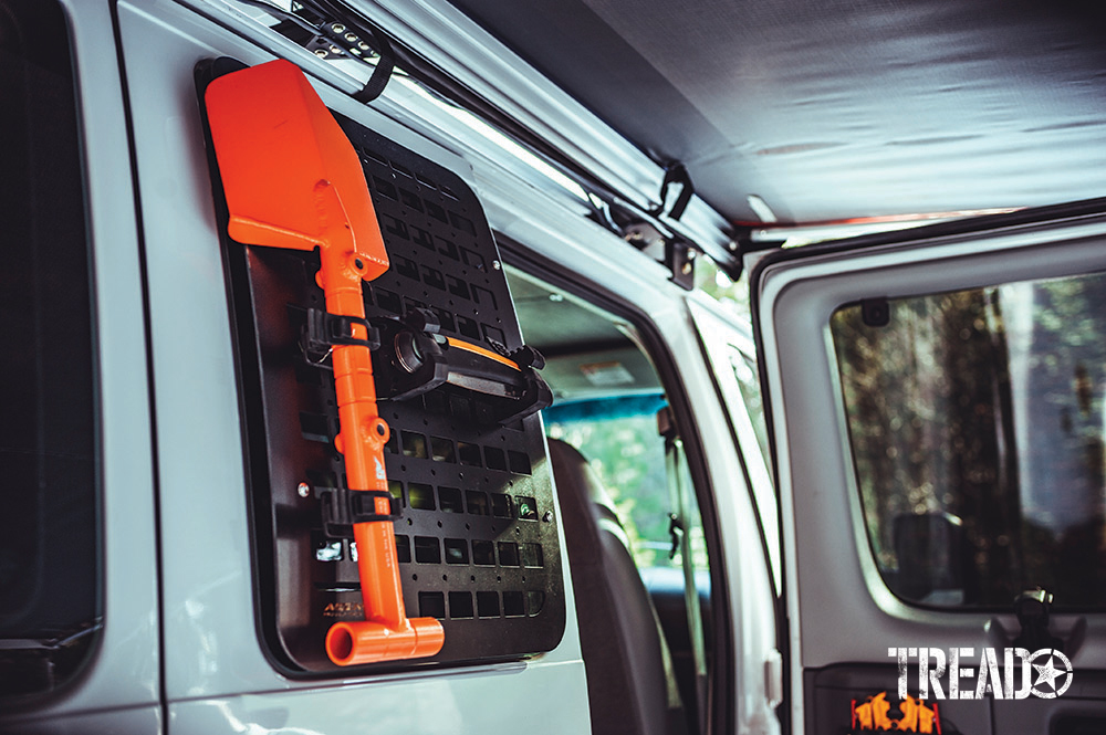 Agency 6 black GRIDS MOLLE and orange shovel is mounted on a read white van door.