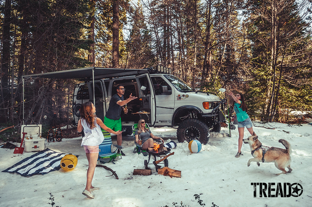 The Montes family are playing catch next to their 2006 Ford E350 Super Duty 4x4 while at camp in the woods.