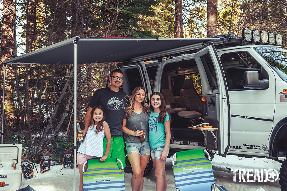 The white Ford E350 Super Duty 4x4 van sits behind Ken Montes and family, leaning on striped camp chairs.