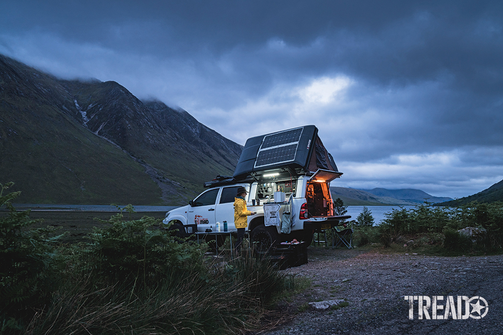 Preparing dinner next to a customized white Toyota and rooftop tent while overlooking the water and nearby green hills.