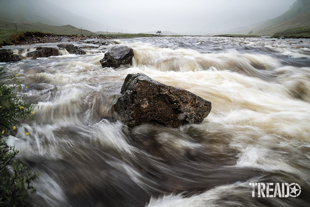 Scotland's quick-moving waterway show whitewater zipping through large boulders in front of gray skies.