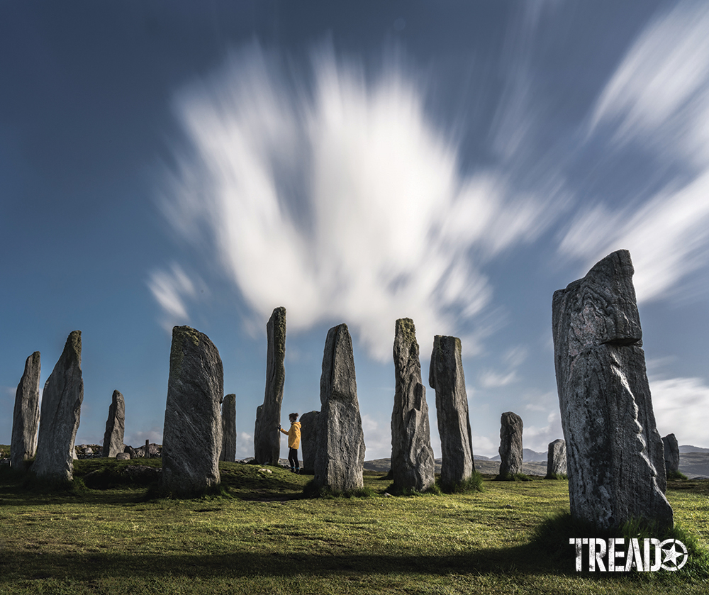 The Callanish Standing Stones loom over short green grasses while some clouds wisp away overhead.