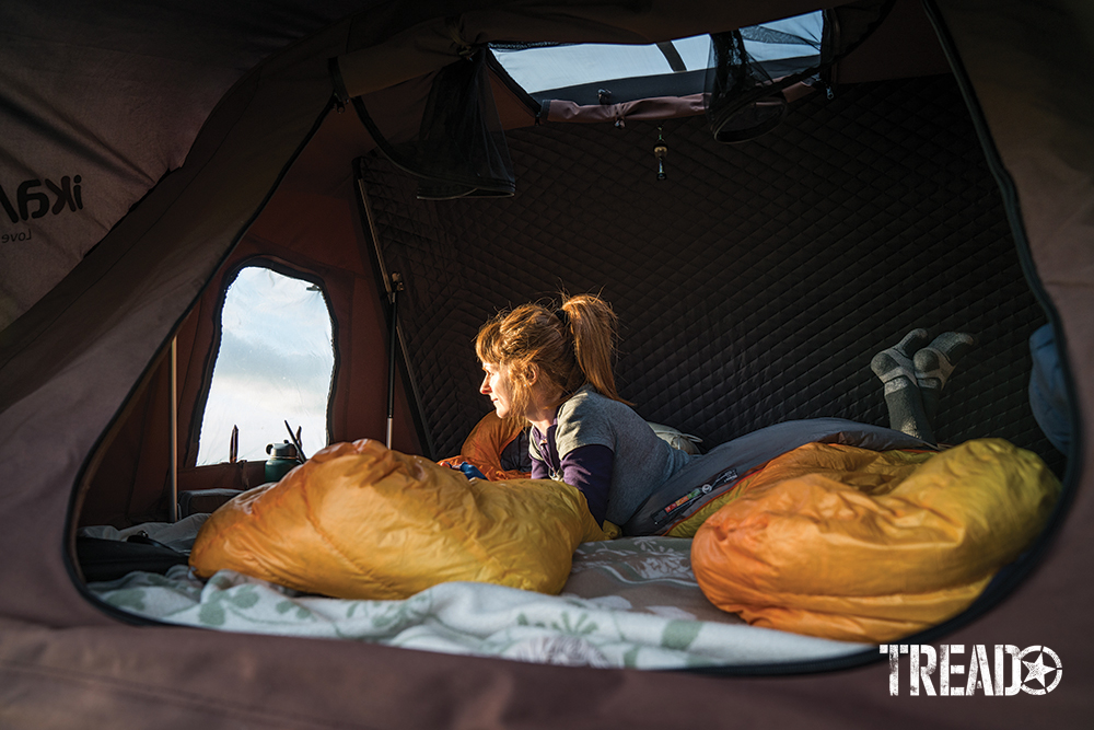 Opened rooftop tent with woman looking outward, two yellow sleeping bags laid out ready for sleep.