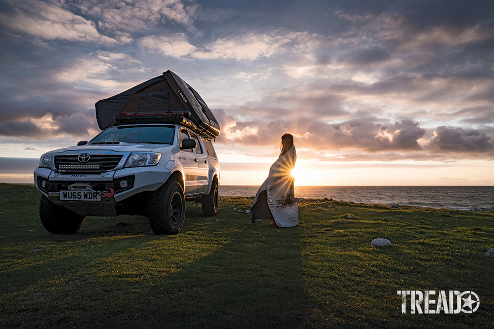 A white customized Toyota with rooftop tent sits on green grass next to water with the sun setting in clounds and behind woman in blanket.