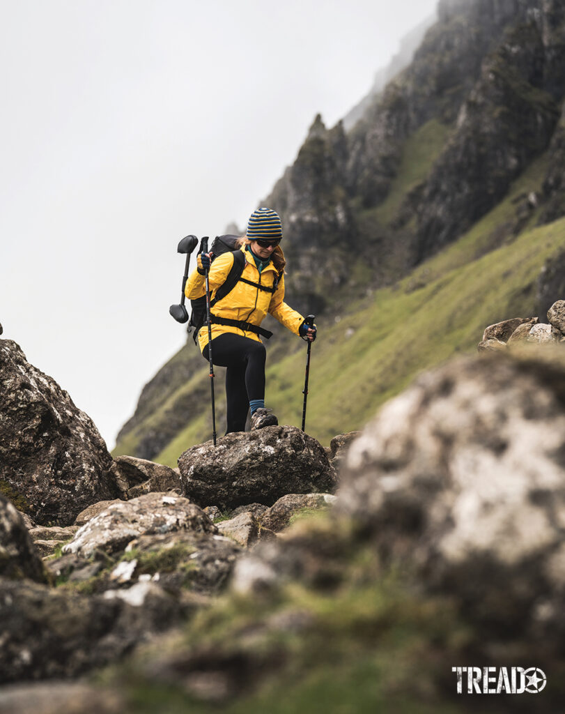 Hiker in yellow jacket, black pants, and backpack hikes a Scottish landslide area on big rocks.