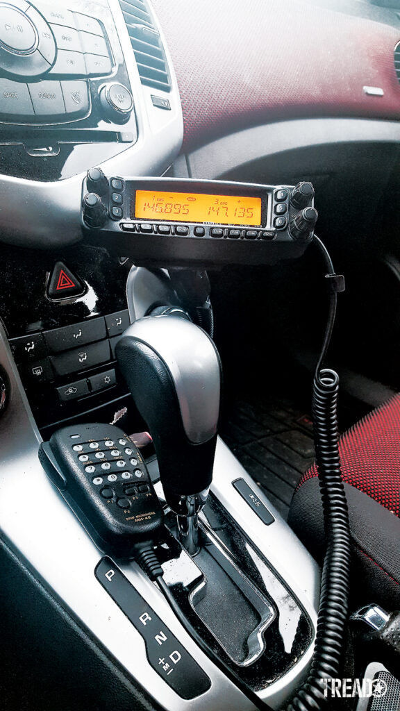 A hardwired radio is mounted near the center of a vehicle with a silver, gray, and red interior.