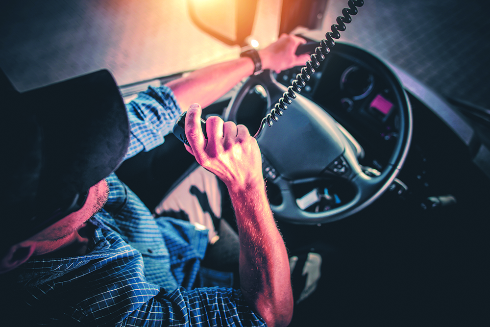A man grabs the mounted radio's receiver with his right hand while driving.