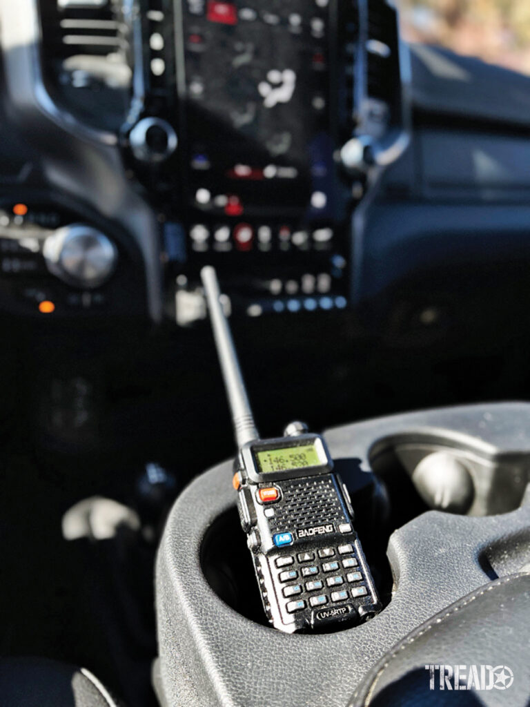 This black handheld radio sits in a centrally located gray cup holder.