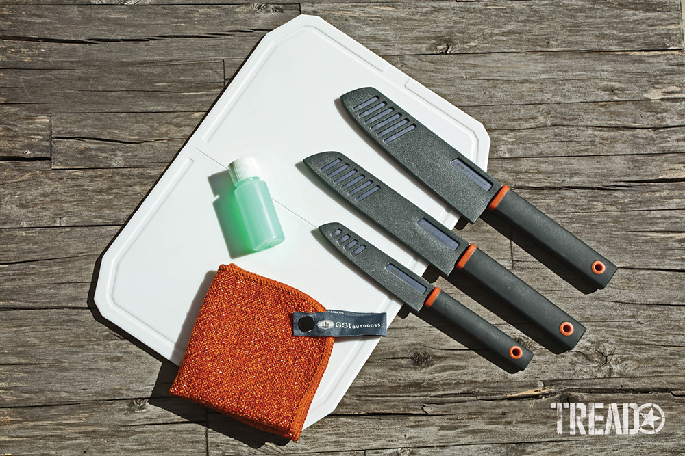 This knife set comes with a white cutting board, three knives as well as orange square dishcloth and bottle for soap.