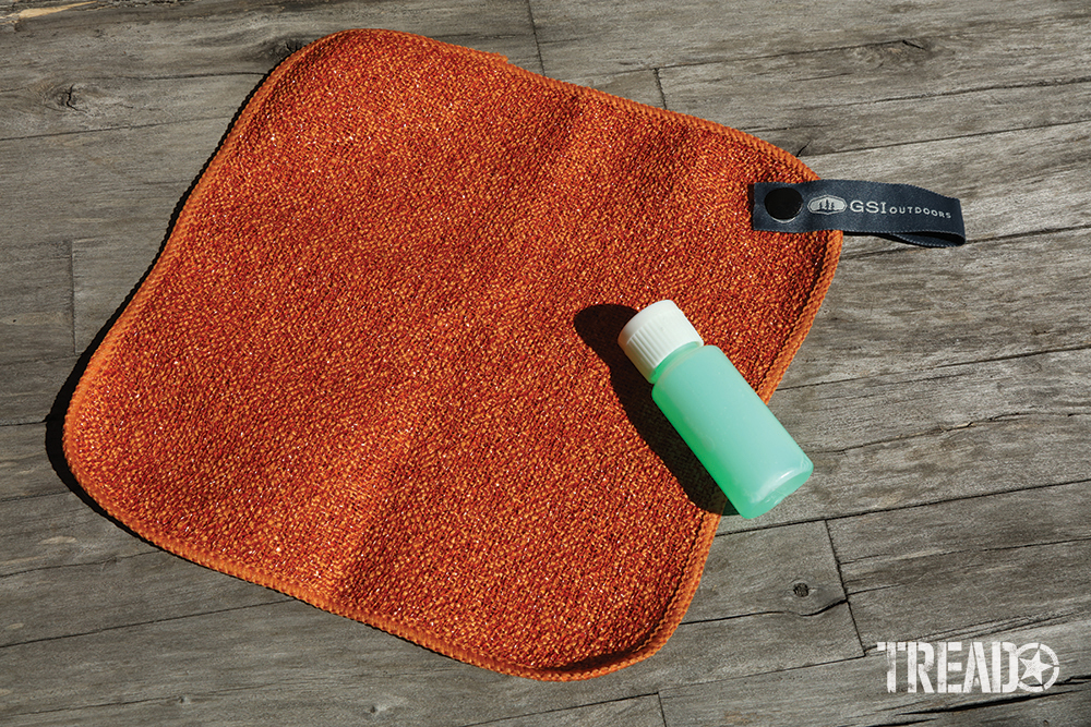 This knife set includes an orange square dish cloth and mint green small bottle for dish soap.