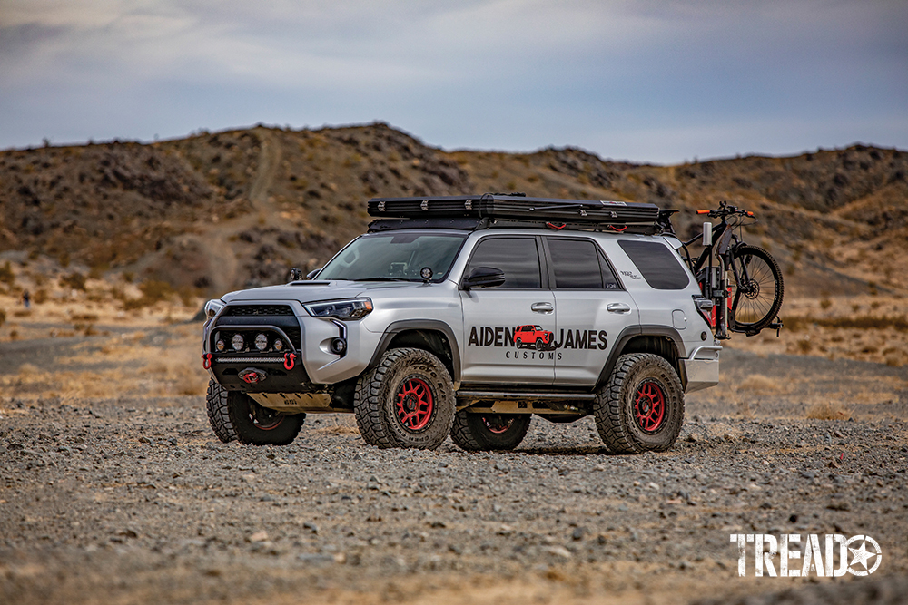 Black and red accents this silver customized 4Runner with black rooftop tent and rear bicycle carrier.