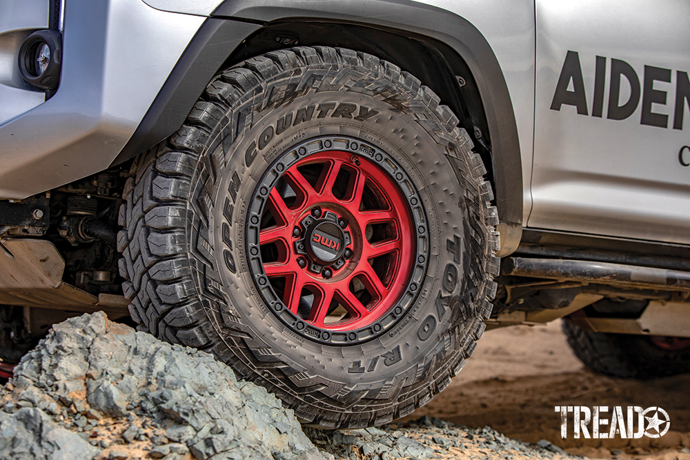 17-inch KMC candy red wheels and beefy Toyo Tires Open Country off-road tires sit on two large rocks.