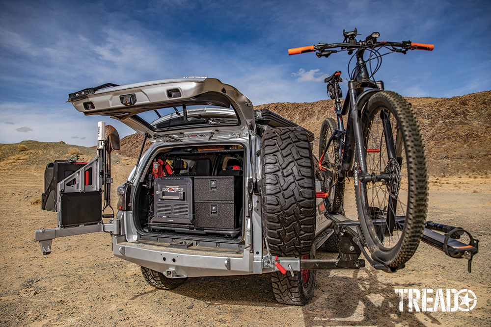 Family camping gear and off-road essentials are neatly stored in back, along with the Dometic fridge/freezer as the dual swing-away tire and jerry car carrier.
