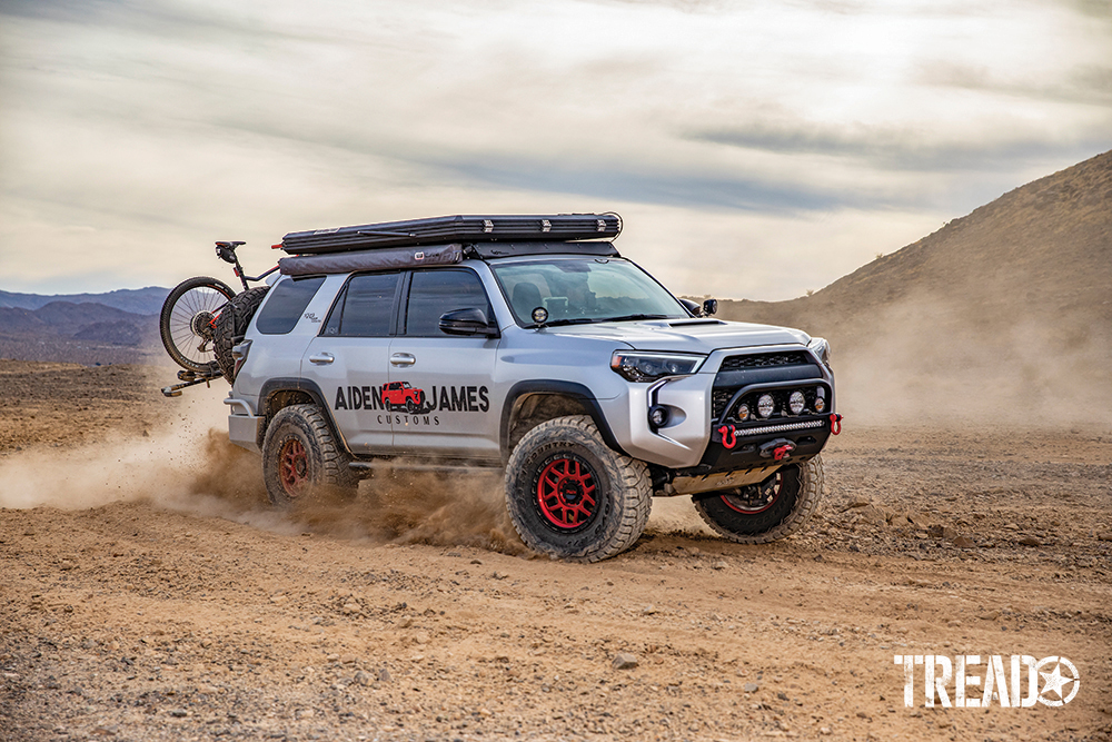 A silver customized 2017 Toyota 4Runner with slim rooftop tent, red wheels, drives through dusty conditions.