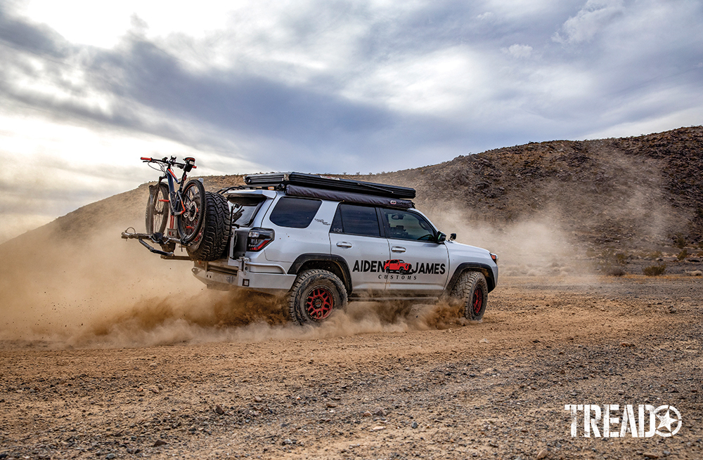 A silver customized 2017 Toyota 4Runner with slim rooftop tent and red wheels, slashes through the dirt.