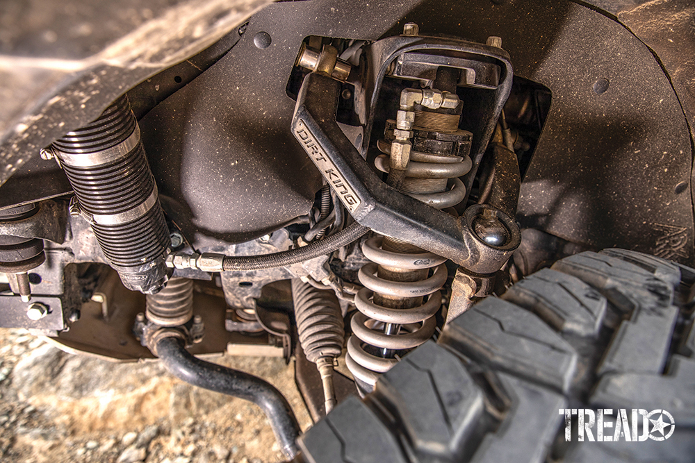 Dirt King Fabrications upper control arms and Radflo shocks hide behind a knobby off-road tire.