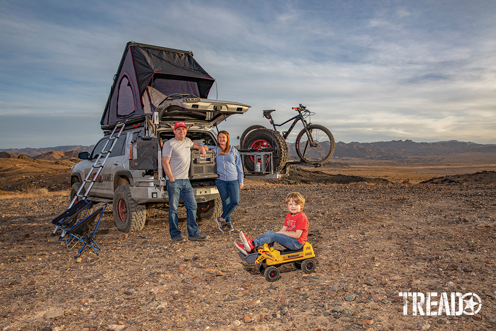 Customized 2017 Toyota 4Runner has rooftop tent opened and tailgate opened while the Fisher family stands in front of it with young boy sitting on bulldozer toy.