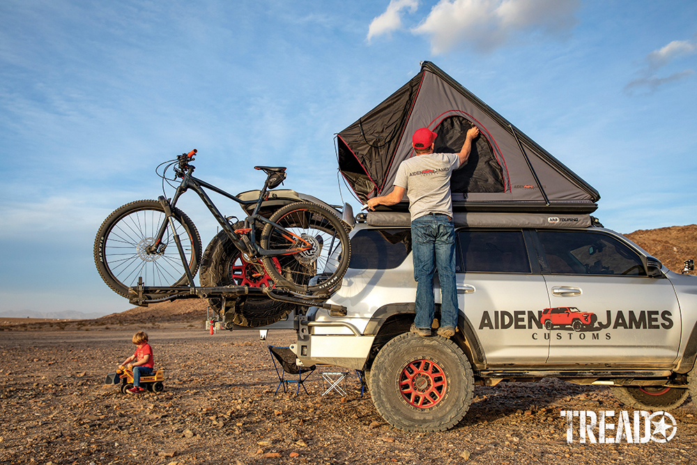 A child with bulldozer toy plays next to a silver adventure 4Runner with bicycles and man zipping up rooftop tent window.