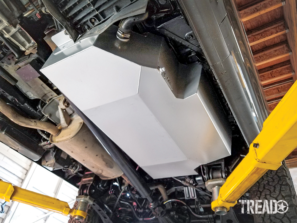The Mitsubishi Delica Space Gear's silver LRA replacement tank is installed and photographed while on vehicle lift with yellow arms.