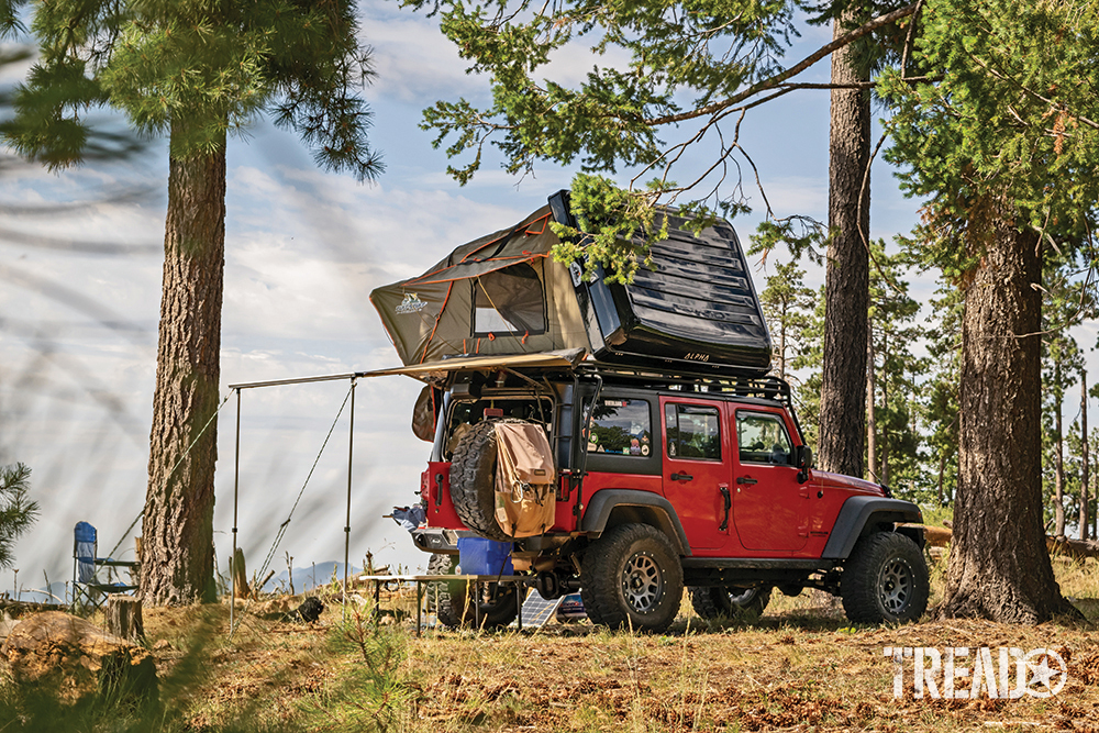 A red Jeep with awning and black-encased rooftop tent is camping near Payson, Arizona.
