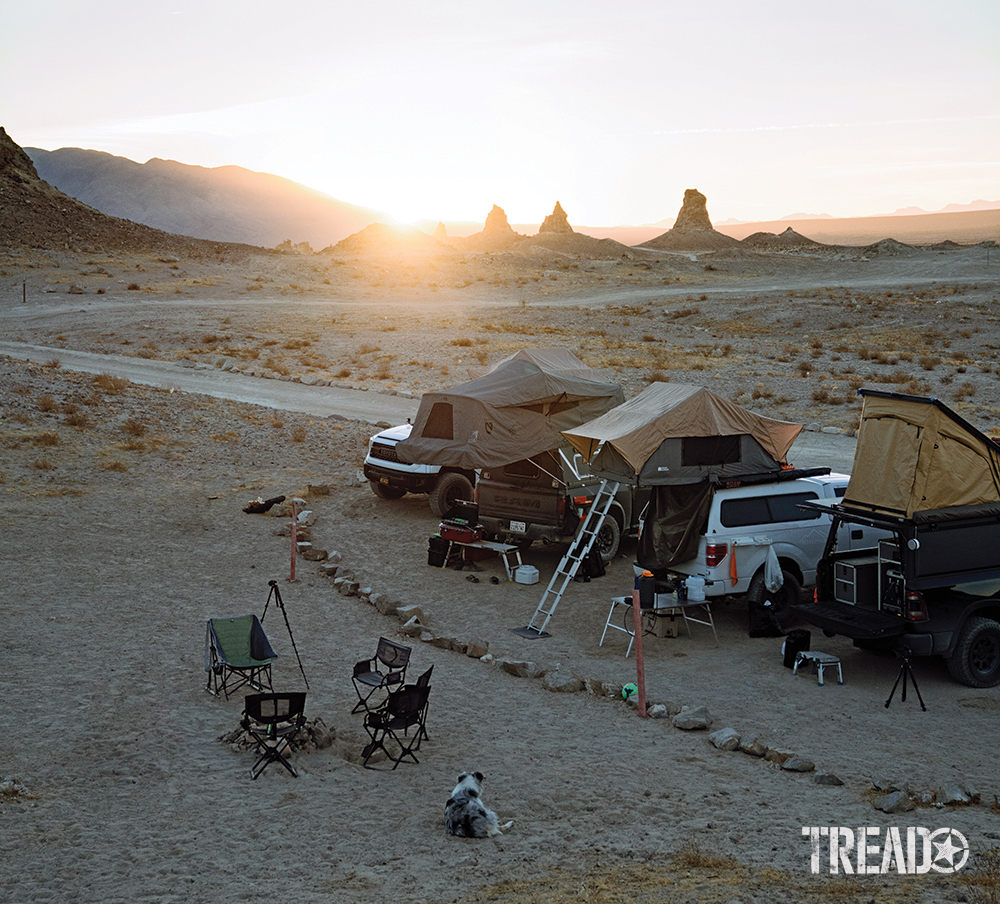 Four adventure vehicles are parked in a desert remote camp area, waiting for the sun to go down.