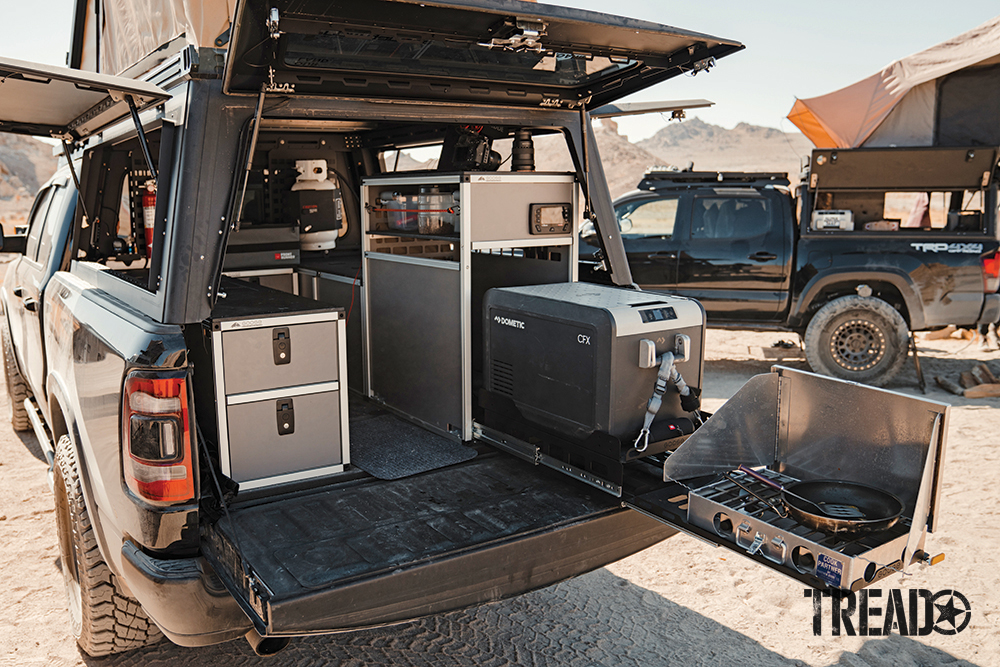 Along with a pull-out kitchen setup, this RAM truck features a tan hard-sided rooftop tent and various storage cubbies.