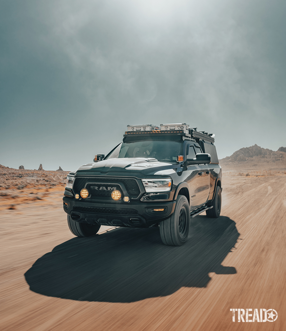 This adventure-ready truck can tackle trails on the dirt, sand, snow, and everything in between. It's driving quickly on dirt trails as the sun beats behind it.